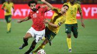 Penyerang Mesir, Mohamed Salah berebut bola dengan pemain Afrika Selatan, Dean Furman, Minggu (7/7/2019). Pada laga tersebut Mesir tersingkir dari gelaran Piala Afrika 2019 usai kalah 0-1 dari Afrika Selatan. [Khaled DESOUKI / AFP]