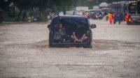 Warga menaiki mobil saat melintasi genangan banjir di Jalan DI Panjaitan, Cawang, Rabu (1/1/2020). Banjir tersebut disebabkan karena tingginya intensitas hujan yang mengguyur sejak Selasa (31/12/2019). (ANTARA FOTO/Aprillio Akbar)